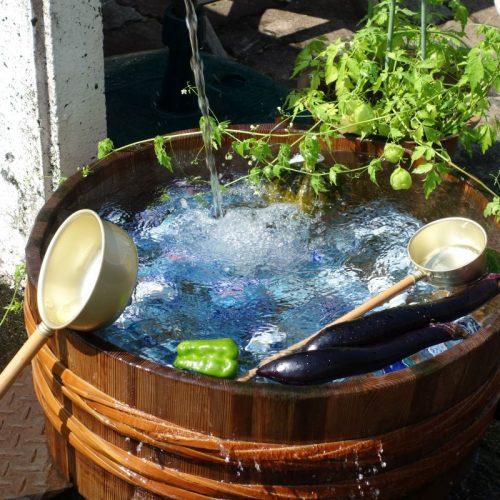 Wasserfass mit frischem Gemüse und Ramuneflaschen am Grund